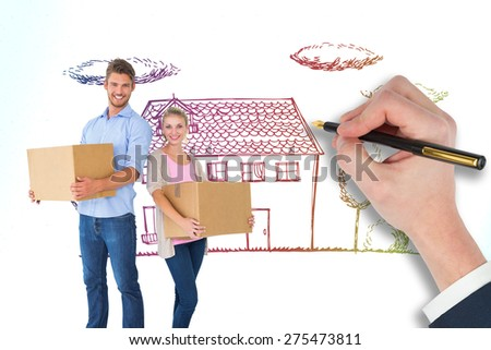 Attractive young couple carrying moving boxes against grey