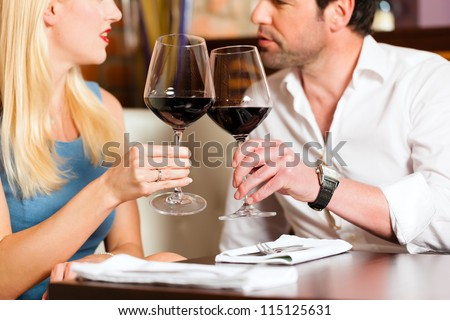 Attractive young couple drinking red wine in restaurant or bar, it might be the first date - stock photo
