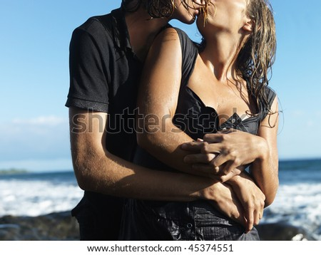 Attractive young couple embracing and kissing each other while standing on rocky coast. Horizontal shot. - stock photo