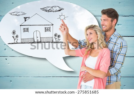 Attractive young couple embracing and pointing against blue sky - stock photo