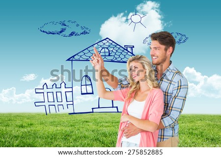 Attractive young couple embracing and pointing against blue sky over green field - stock photo