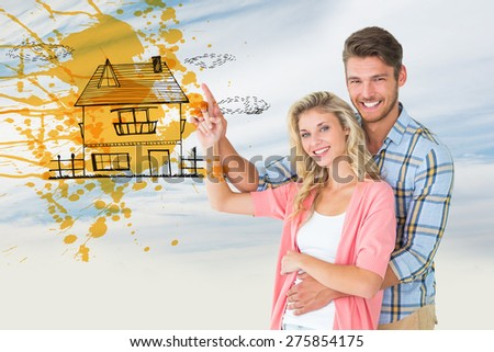 Attractive young couple embracing and pointing against blue sky with clouds - stock photo