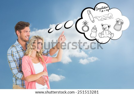 Attractive young couple embracing and pointing against cloudy sky - stock photo