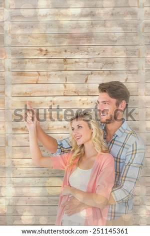 Attractive young couple embracing and pointing against light glowing dots design pattern - stock photo
