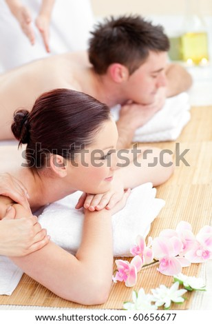 Attractive young couple enjoying a back massage in a spa center - stock photo