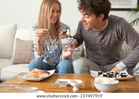 Attractive young couple enjoying eating Japanese sushi and maki food at home, sitting on a white couch in a home living room, sharing food and having a good time, smiling together. Eating fresh food.
