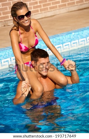 Attractive young couple enjoying summer holiday in swimming pool, smiling, having fun. - stock photo