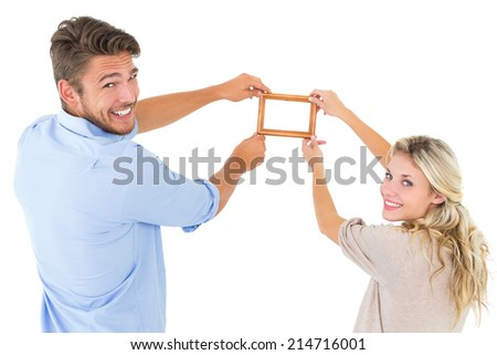 Attractive young couple hanging a frame on white background - stock photo