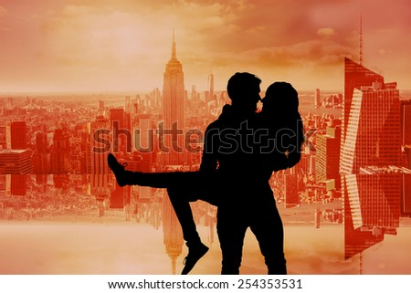 Attractive young couple having fun against room with large window looking on city - stock photo