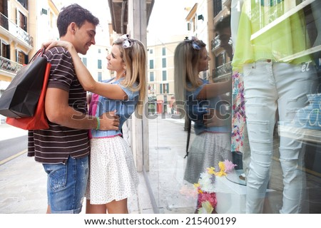 Attractive young couple having fun and enjoying a vacation city break, embracing and smiling while shopping in the fashion stores, outdoors. Consumer and travel lifestyle. - stock photo