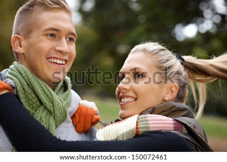 Attractive young couple having fun in park, smiling.