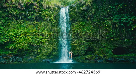 Attractive young couple having fun relaxing at beautiful waterfall