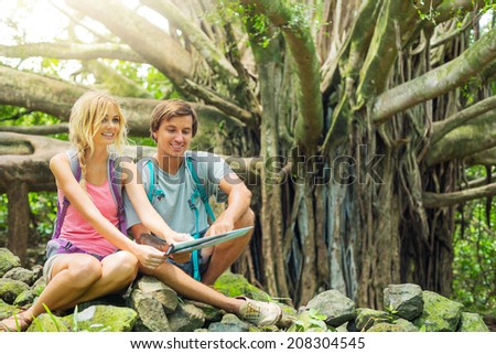 Attractive young couple having fun together outdoors on hike looking at map - stock photo