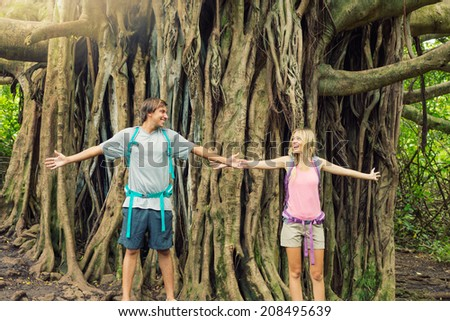Attractive young couple having fun together outdoors on hike, standing in front of giant banyan tree. - stock photo