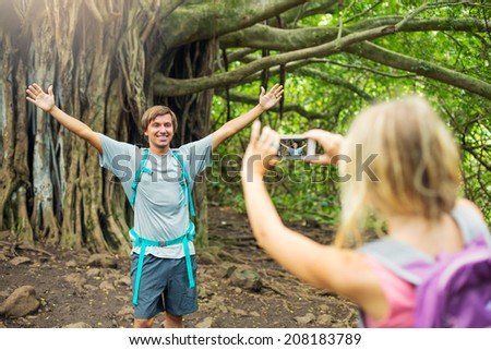 Attractive young couple having fun together outdoors on hike. Taking a picture with camera phone. - stock photo