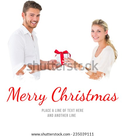 Attractive young couple holding a gift against merry christmas - stock photo