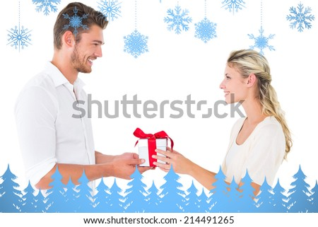 Attractive young couple holding a gift against snowflakes and fir trees in blue - stock photo
