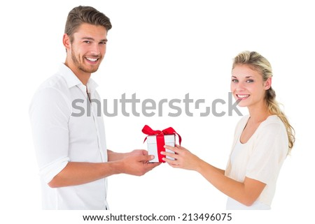 Attractive young couple holding a gift on white background - stock photo