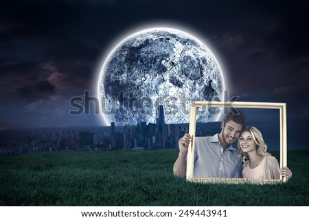 Attractive young couple holding picture frame against bright moon over city - stock photo