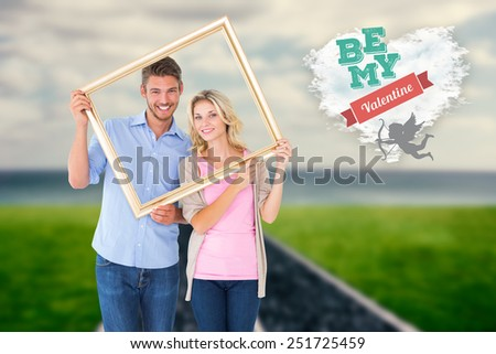 Attractive young couple holding picture frame against cloud heart - stock photo