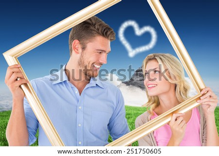 Attractive young couple holding picture frame against clouds over mountain peak - stock photo