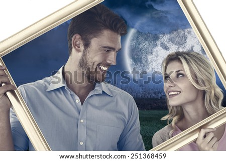 Attractive young couple holding picture frame against large moon over city - stock photo