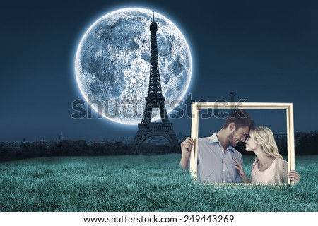 Attractive young couple holding picture frame against large moon over paris - stock photo