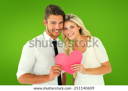 Attractive young couple holding pink heart against green vignette - stock photo