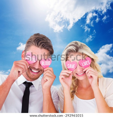 Attractive young couple holding pink hearts over eyes against blue sky - stock photo