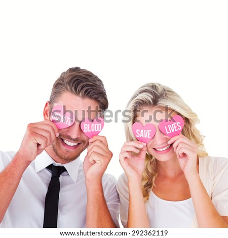 Attractive young couple holding pink hearts over eyes against donate blood save lives - stock photo