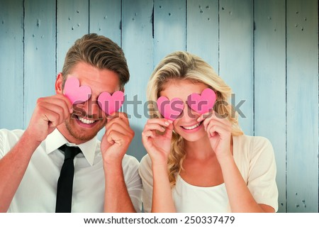 Attractive young couple holding pink hearts over eyes against wooden planks - stock photo