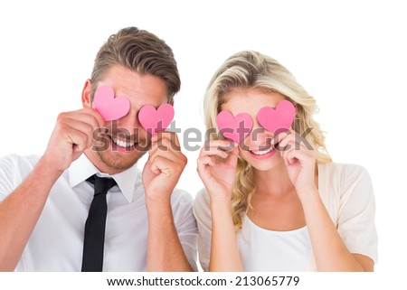 Attractive young couple holding pink hearts over eyes on white background - stock photo