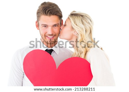 Attractive young couple holding red heart on white background - stock photo