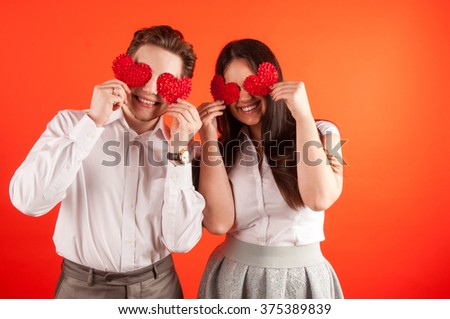 Attractive young couple holding red hearts over eyes against red background - stock photo