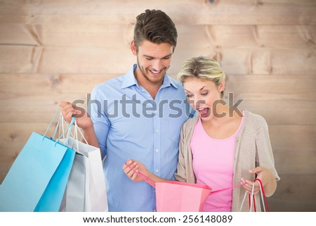 Attractive young couple holding shopping bags against bleached wooden planks background - stock photo