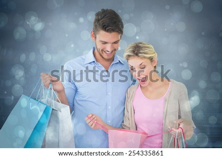 Attractive young couple holding shopping bags against blue abstract light spot design - stock photo