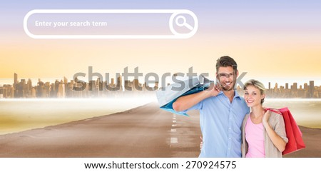 Attractive young couple holding shopping bags against city on the horizon - stock photo