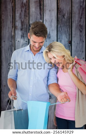 Attractive young couple holding shopping bags against grey wooden planks - stock photo