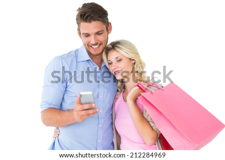 Attractive young couple holding shopping bags looking at smartphone on white background - stock photo