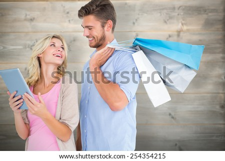 Attractive young couple holding shopping bags looking at tablet pc against bleached wooden planks background - stock photo