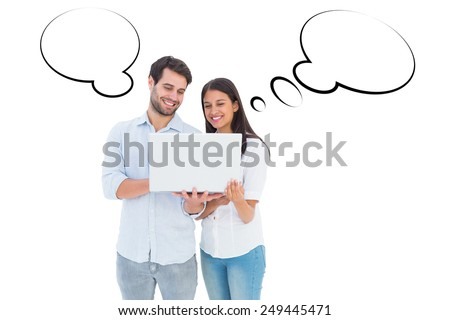 Attractive young couple holding their laptop against speech bubble - stock photo