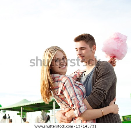 Attractive young couple hugging and having fun in an amusement park arcade during a sunny day, holding a cotton sugar sweet and turning to the camera smiling. - stock photo