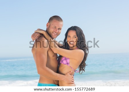 Attractive young couple hugging each other on the beach