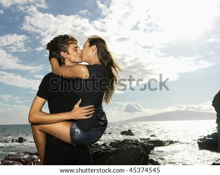 Attractive young couple in a passionate embrace and kissing on a rocky coast. Horizontal shot. - stock photo