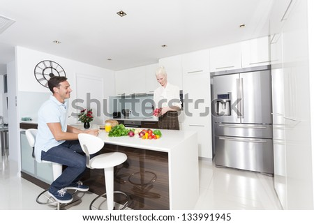 Attractive young couple in modern kitchen - stock photo