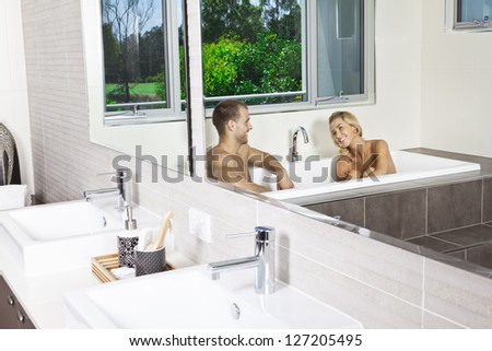 Attractive young couple in stylish bathroom having a bath