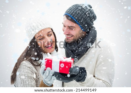 Attractive young couple in warm clothes holding gift against snow falling - stock photo