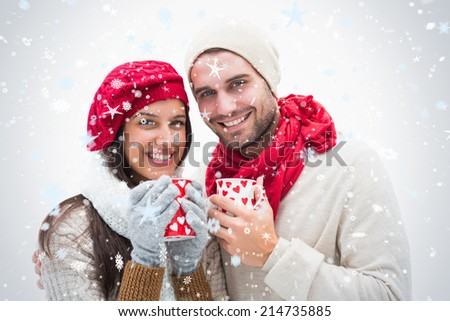 Attractive young couple in warm clothes holding mugs against snow falling - stock photo