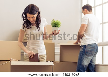 Attractive young couple is moving, smiling and looking through things while packing, standing among cardboard boxes - stock photo