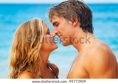 Attractive Young Couple Kissing on Tropical Beach - stock photo